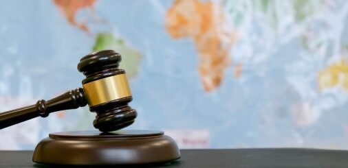 A judge's gavel is in front of a map featuring several countries